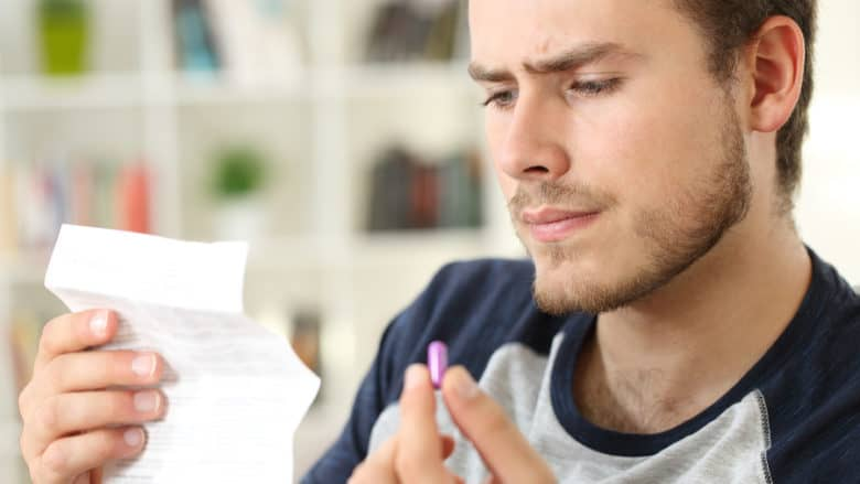 Suspicious Man Reading Leaflet Of A Pill At Home