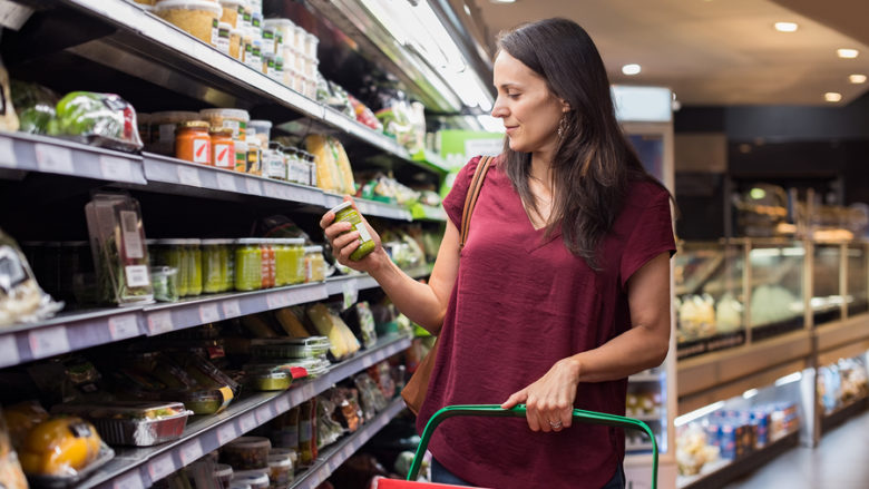 Young woman shopping in grocery store. Mature woman checking foo